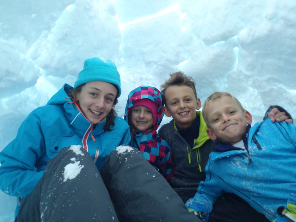 Kids enjoying the igloo they just built.